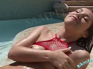 Sweet brunette in fishnet bikini top