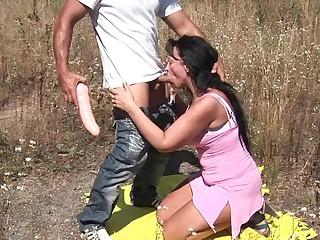 Horny MILF fucking in an open field
